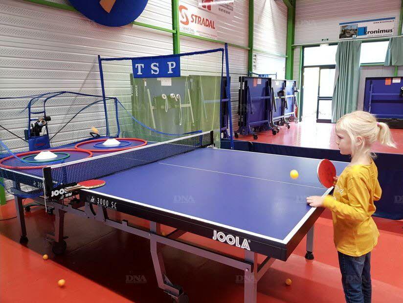La jeune Tabéa, 6 ans, s'essaie au tennis de table avec un robot lanceur de balles.